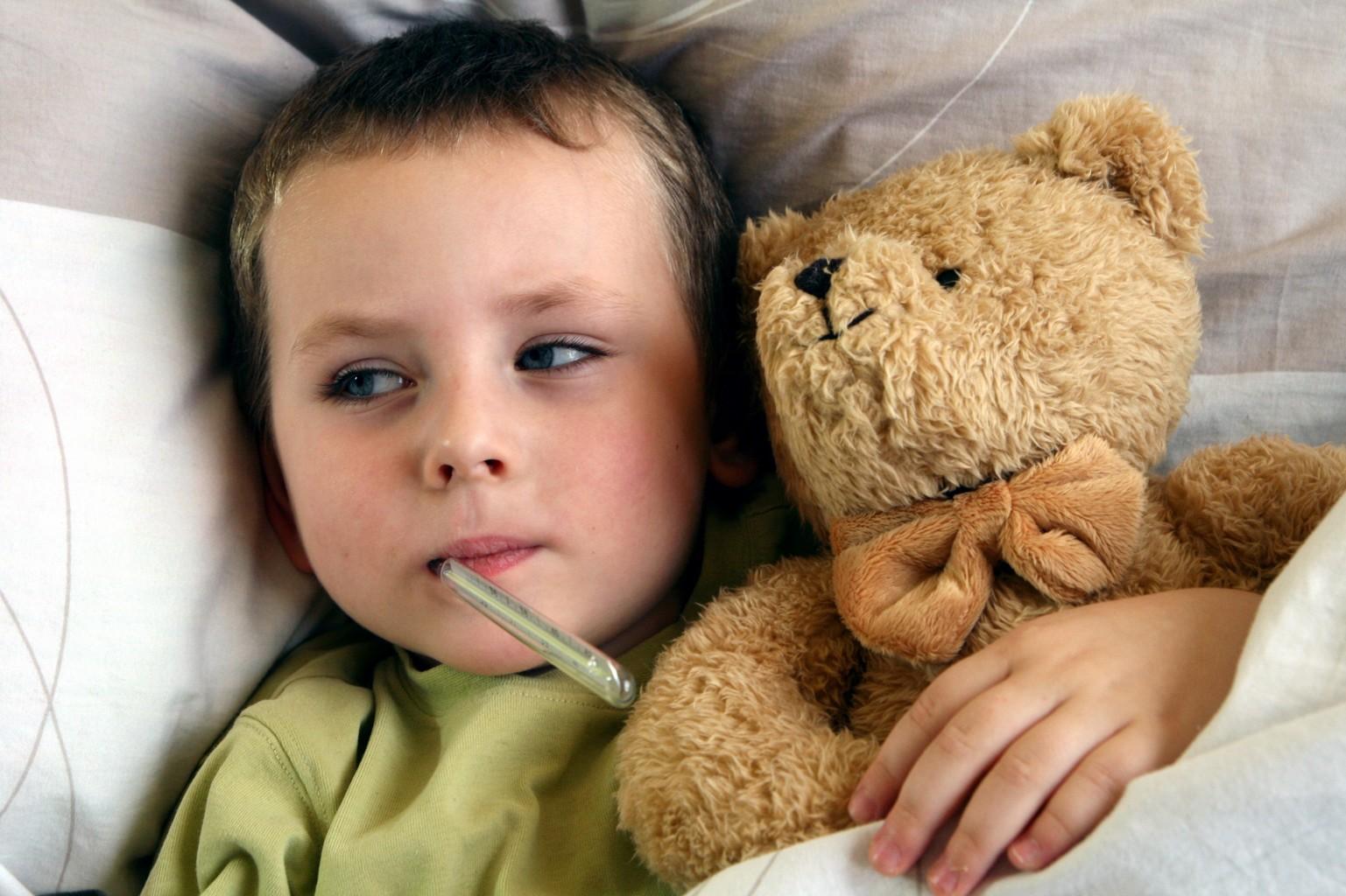 enfant souffrant avec thermomètre dans la bouche et nounours dans les bras